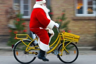 epa03987692 A man wearing a Santa Claus costume rides a bicycle to the Christmas post office inHimmelpfort,Germany, 12 December 2013. About 185,000 Christmas letters coming from all over the world were mailed to the post office so far. All letters arrived before 15 December 2013 will be answered.  EPA/PATRICKPLEUL