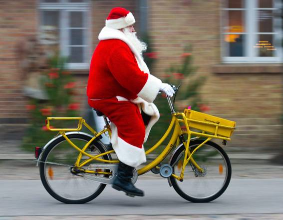 epa03987692 A man wearing a Santa Claus costume rides a bicycle to the Christmas post office in Himmelpfort, Germany, 12 December 2013. About 185,000 Christmas letters coming from all over the world were mailed to the post office so far. All letters arrived before 15 December 2013 will be answered.  EPA/PATRICK PLEUL